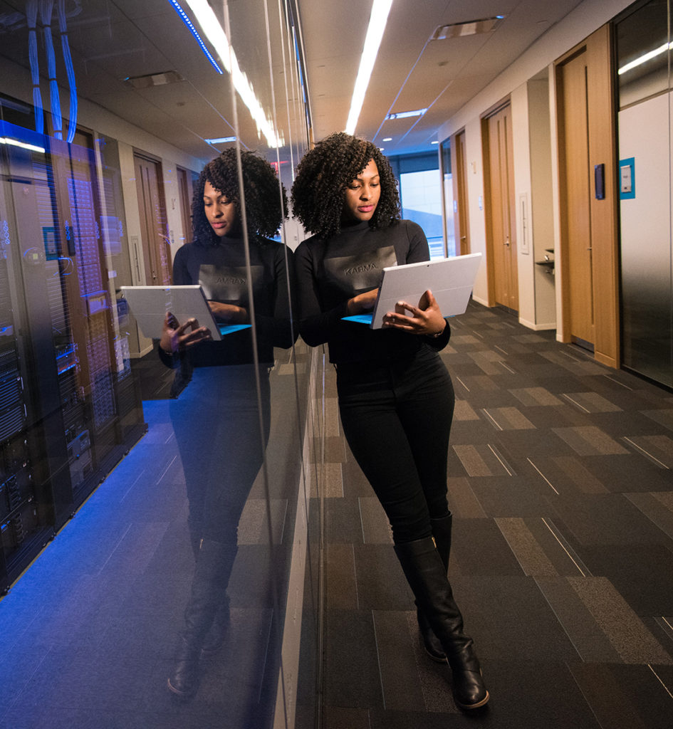 A professional Black woman works in an office hallway on a laptop leaning up agains a glass wall, behind the glass is a server room.