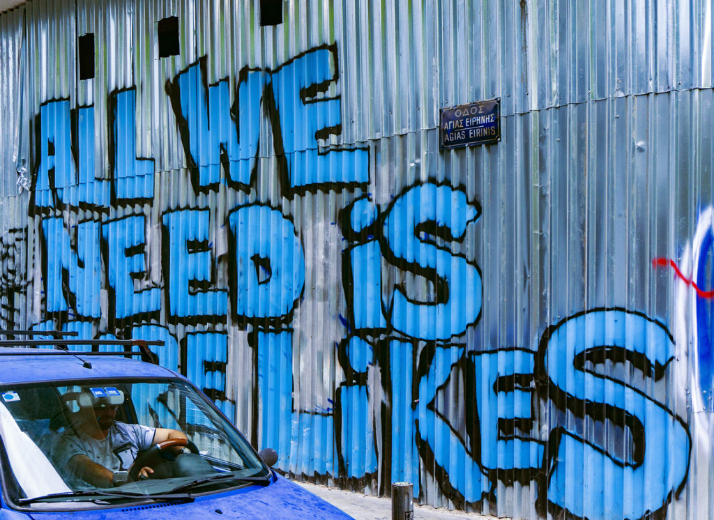 """An industrial wall is spray painted with blue words """"All we need is more likes"""""""