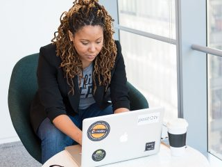 Black professional woman sits at a small table in a high-rise building working on a laptop
